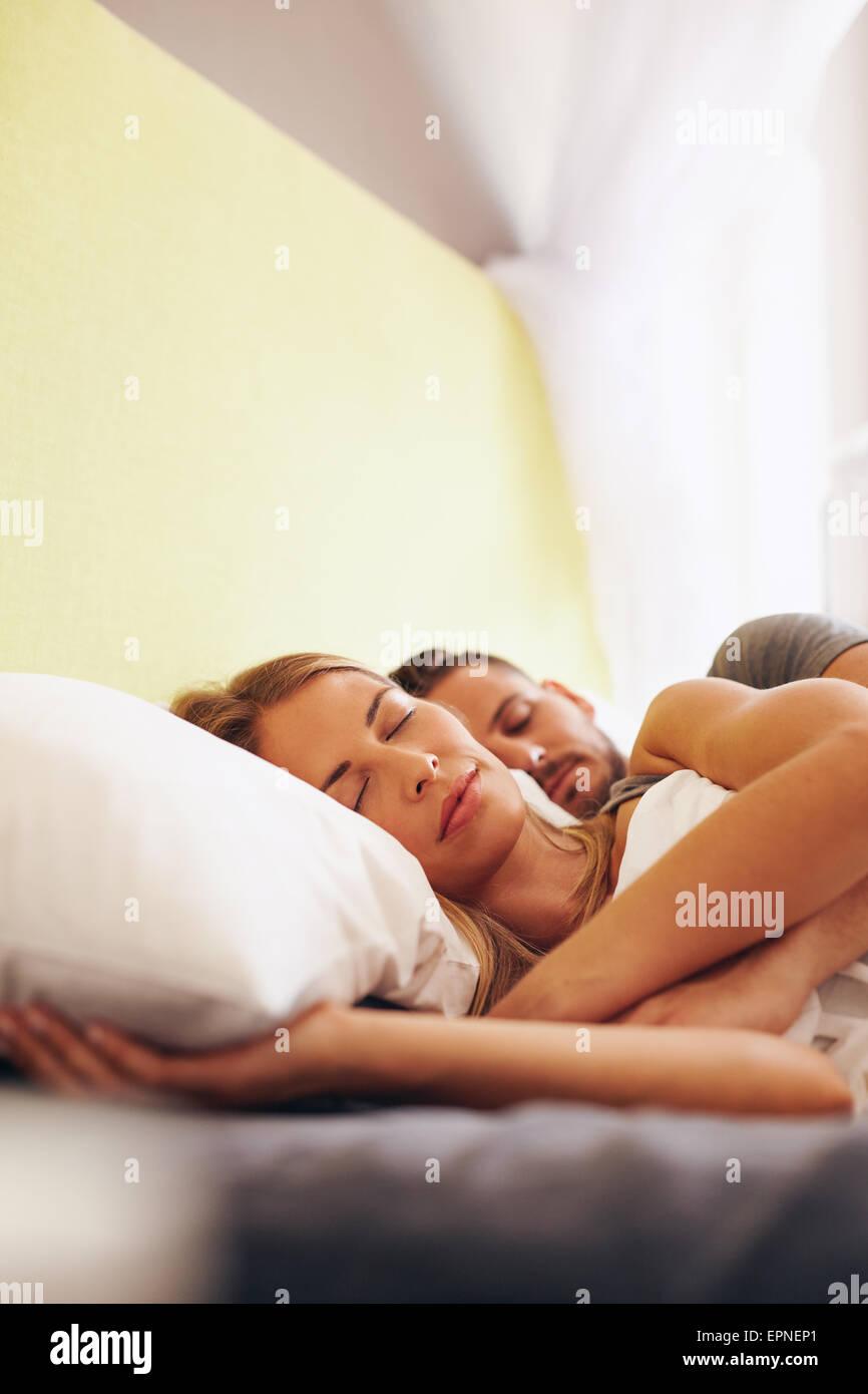 Innenaufnahme der junge Mann und Frau miteinander schlafen im Schlafzimmer. Kaukasische Pärchen auf Bett schlafen. Stockbild