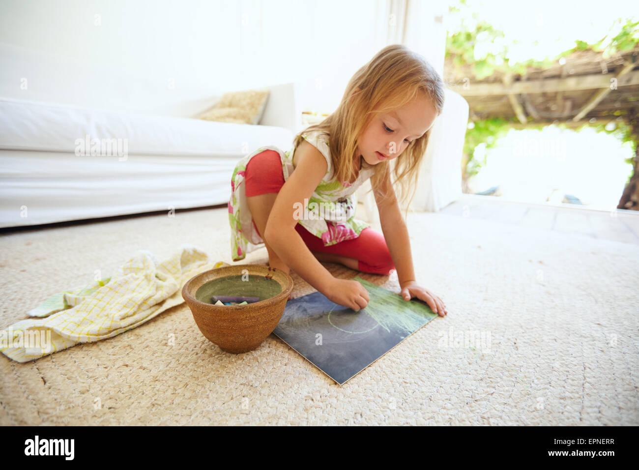 Schuss von unschuldigen kleinen kaukasischen Mädchen am Boden ein Bild mit Farbe Kreide Färbung. Schülerin Stockbild