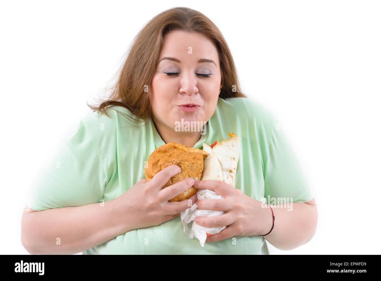 Korpulente Frau, die sucht nach ungesund essen. Glücklich halten einige Kalorien essen. Stockbild