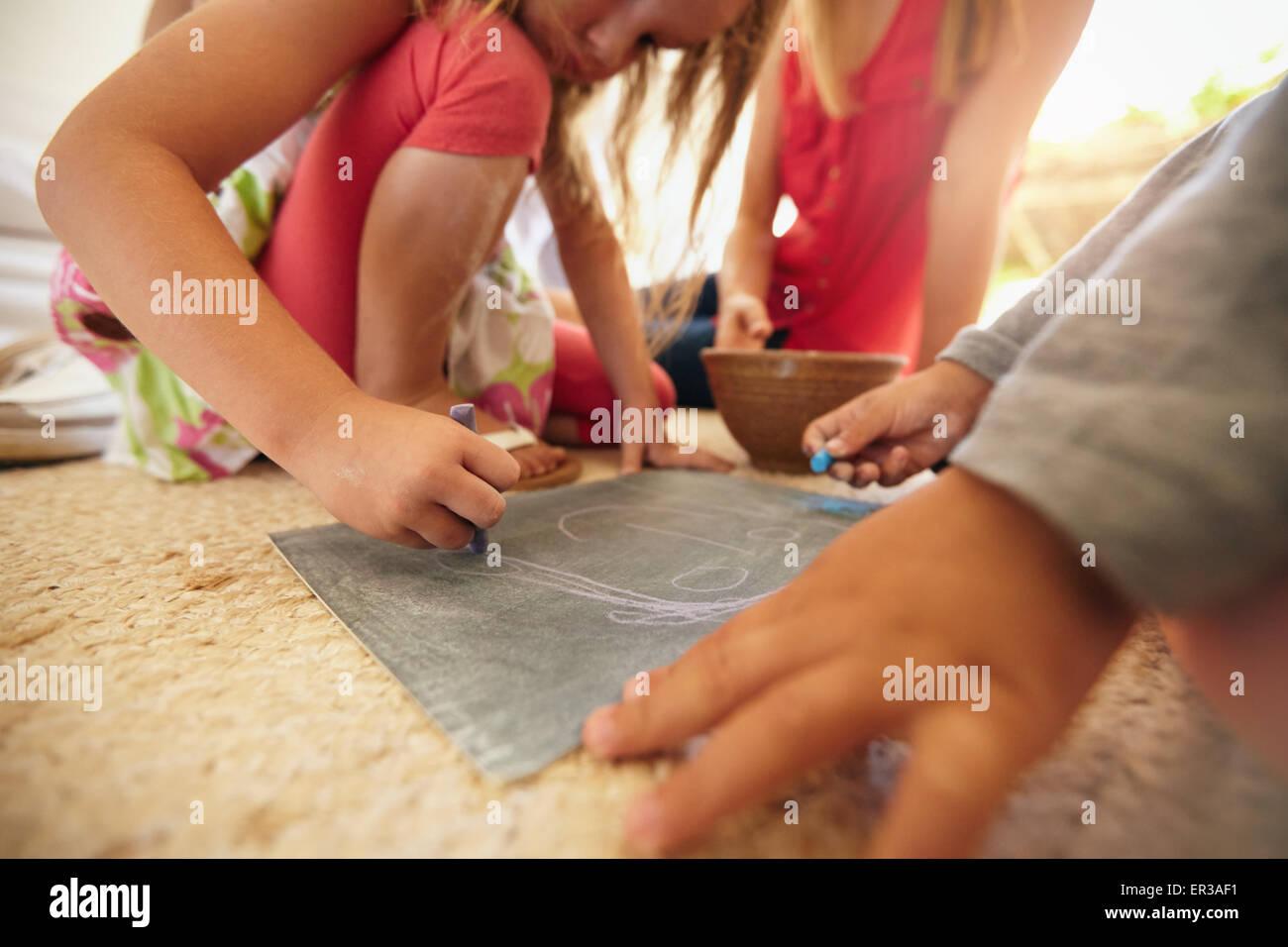 Kleines Mädchen mit ihrem Bruder und Eltern sitzen. Konzentrieren Sie sich auf Mädchen Hände zeichnen Stockbild