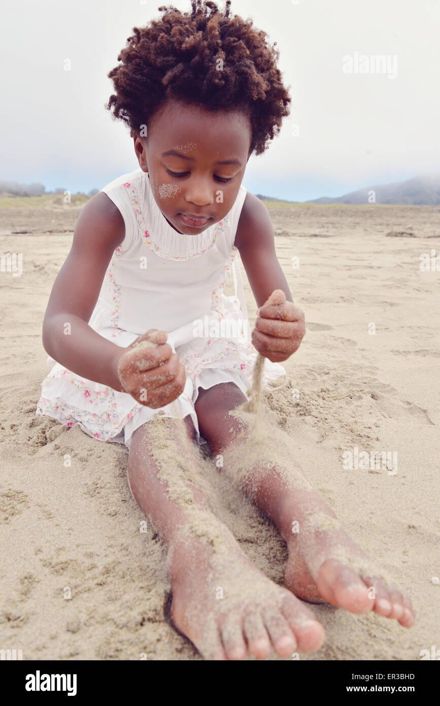 Mädchen sitzen auf einem Strand für ihre Beine mit sand Stockbild