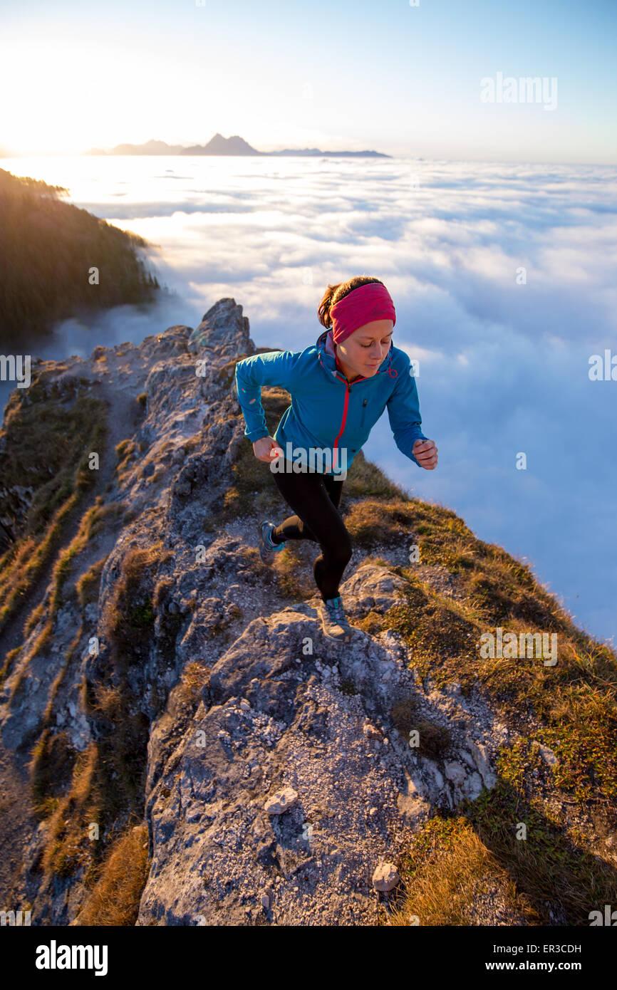 Junge Frau läuft über den Wolken, Salzburg, Österreich Stockbild