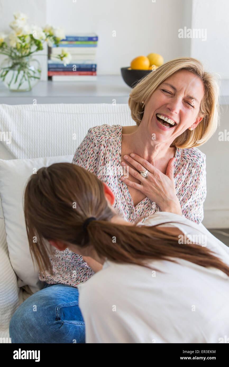 Zwei Frauen lachen; Blick über die Schulter hinter einer Frau. Stockbild