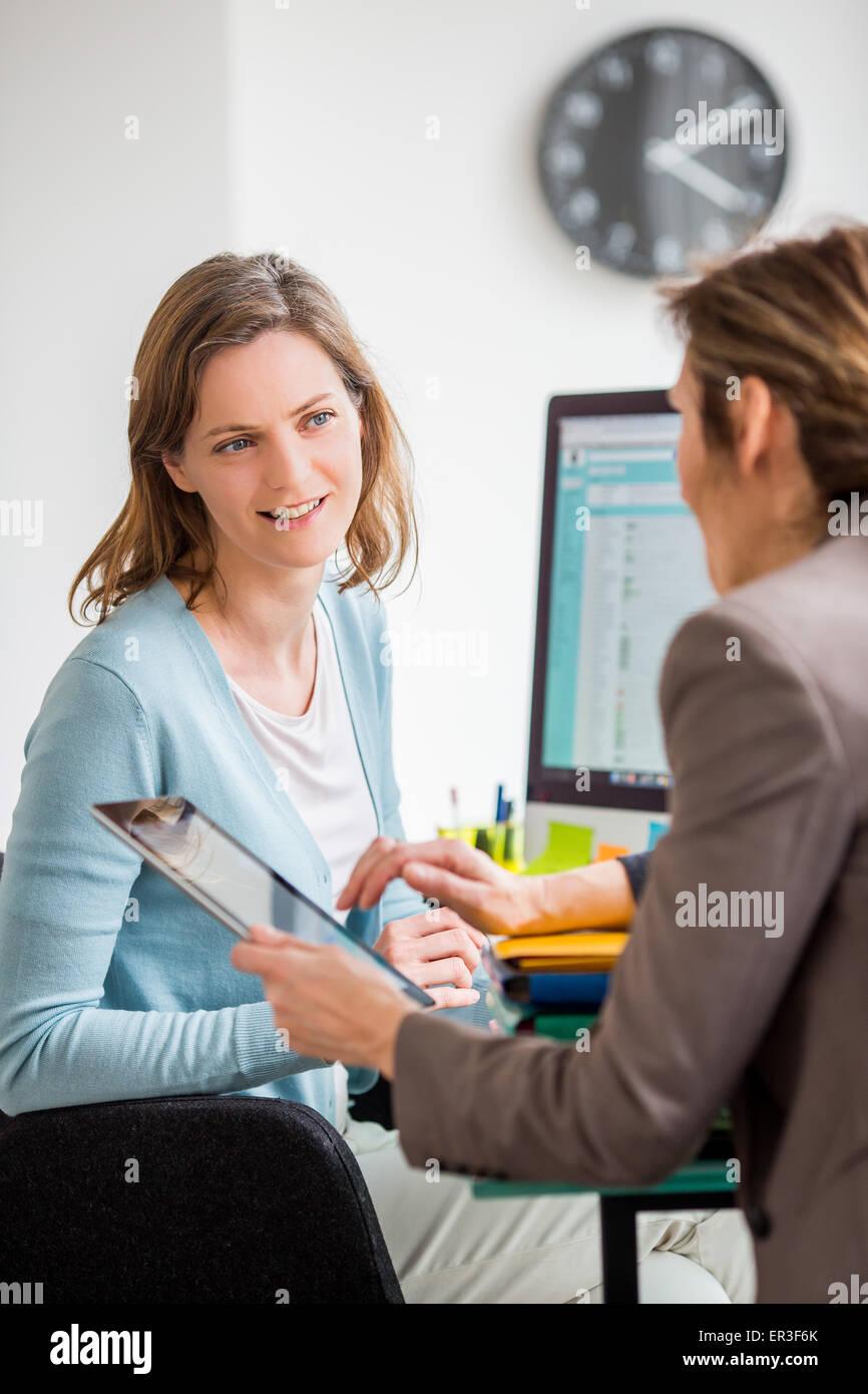 Frauen bei der Arbeit diskutieren. Stockbild