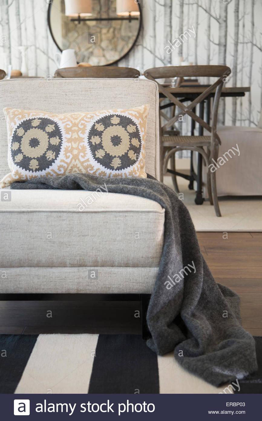 Decke und gemusterten Kissen auf Wohnzimmer Stuhl Stockbild