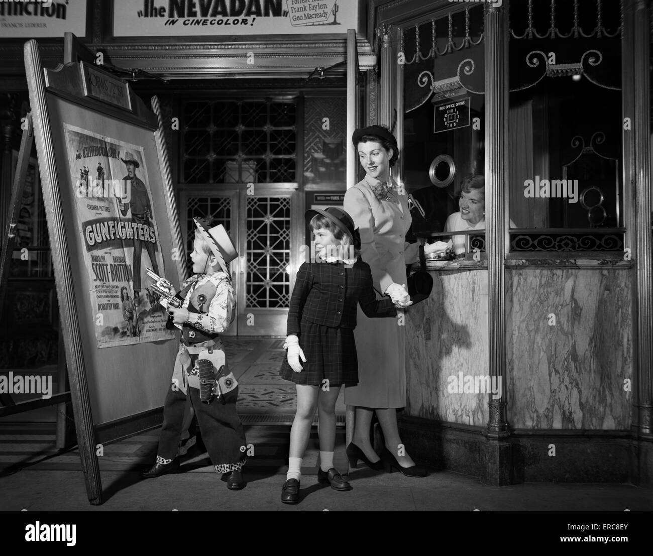1950ER JAHRE KOSTÜM MUTTER NEHMEN KINDER ZUM KAUF VON TICKETS ZU EINEM WESTLICHEN JUNGEN TRAGEN COWBOY FILME Stockbild