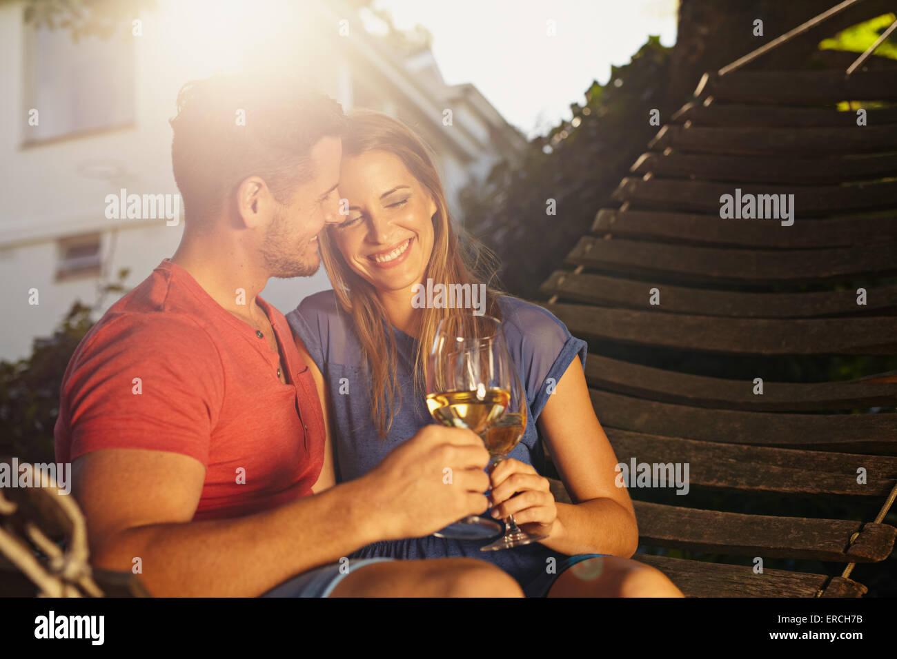 Schöne junge Paar Toasten Wein im Freien. Sie sitzen auf einer Hängematte lächelnd und Weintrinken Stockbild