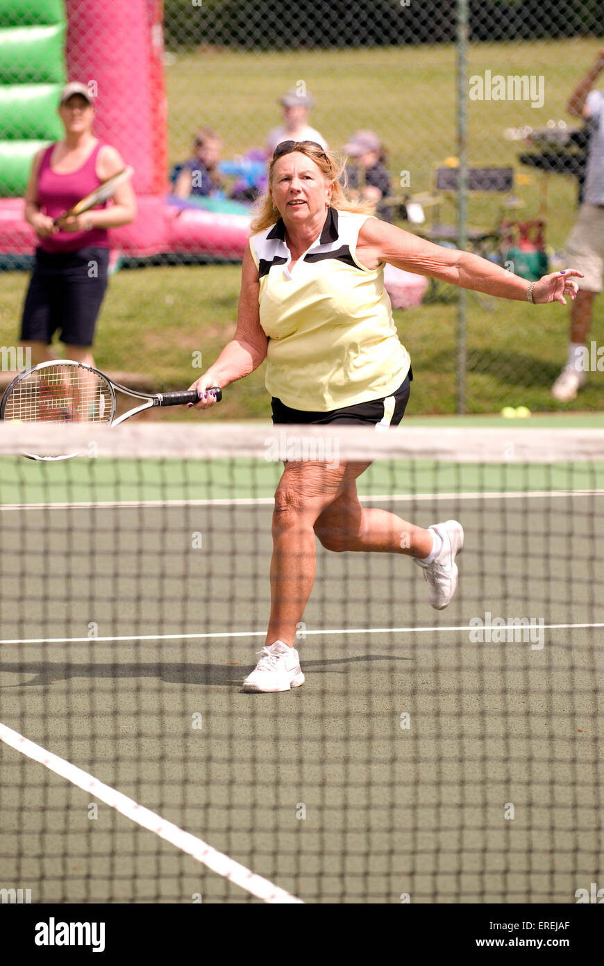 Ältere Frau, die Teilnahme an einem Charity-Tennis-Event, Headley, Hampshire, UK. Stockbild