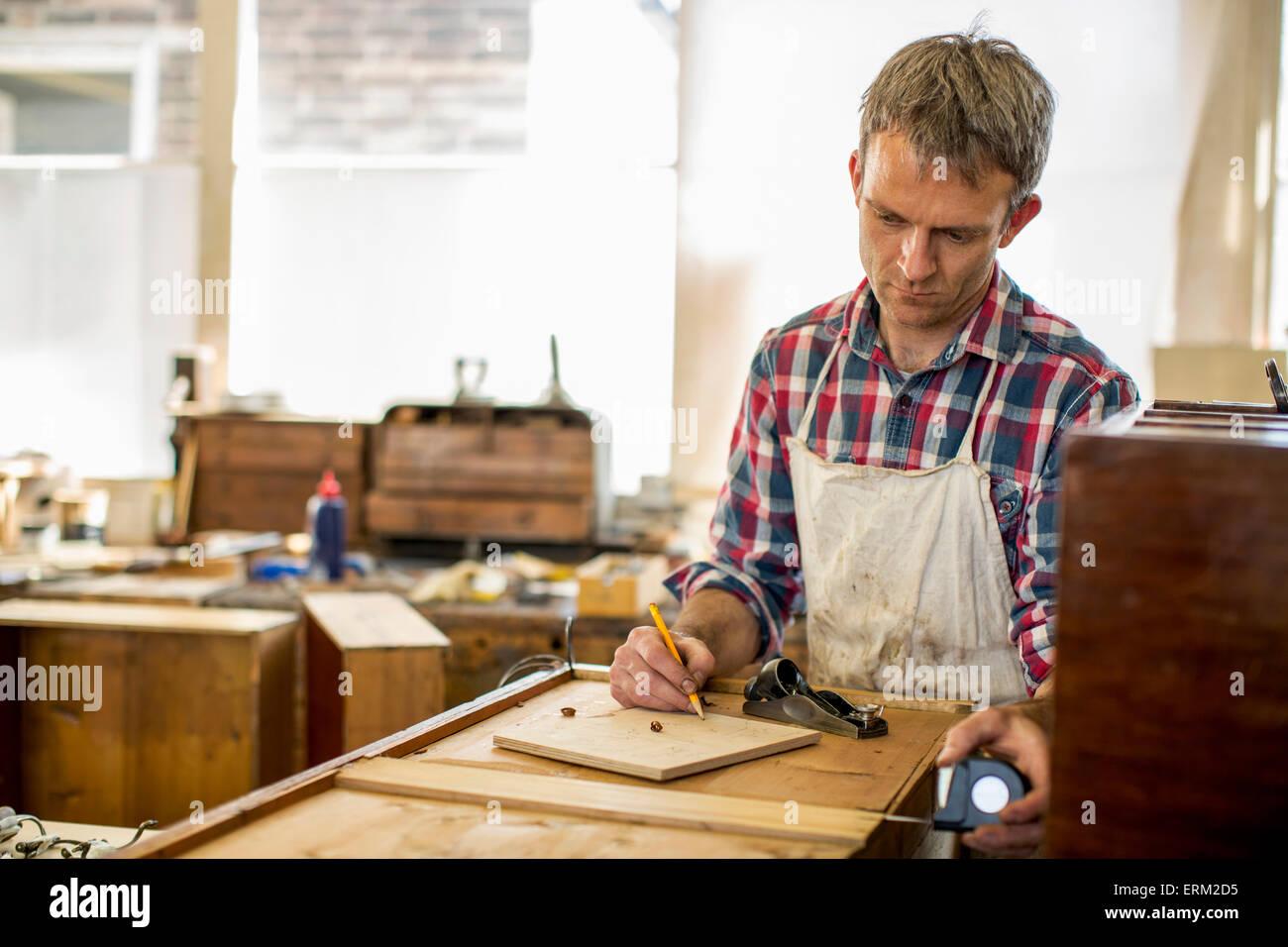 Antike Möbel-Restaurator mit einem Bleistift zeichnen und Planung seiner Arbeit. Stockbild