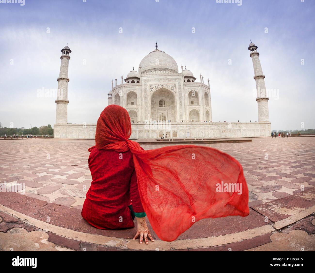 Frau im roten Kostüm mit schmeichelnden Schal sitzt in der Nähe von Taj Mahal in Agra, Uttar Pradesh, Stockbild