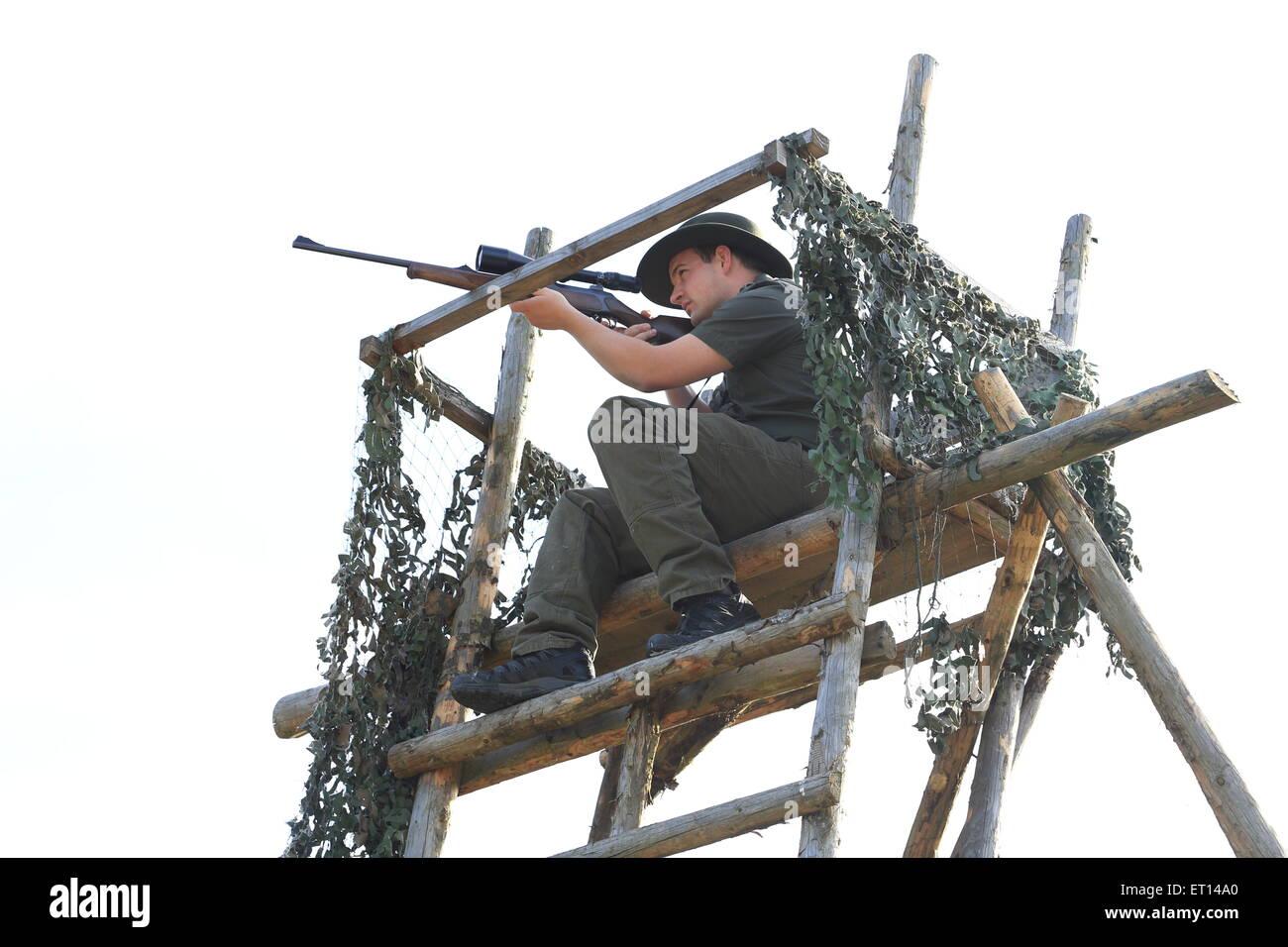 Ein Jäger mit Gewehr auf einem Hochsitz Stockbild