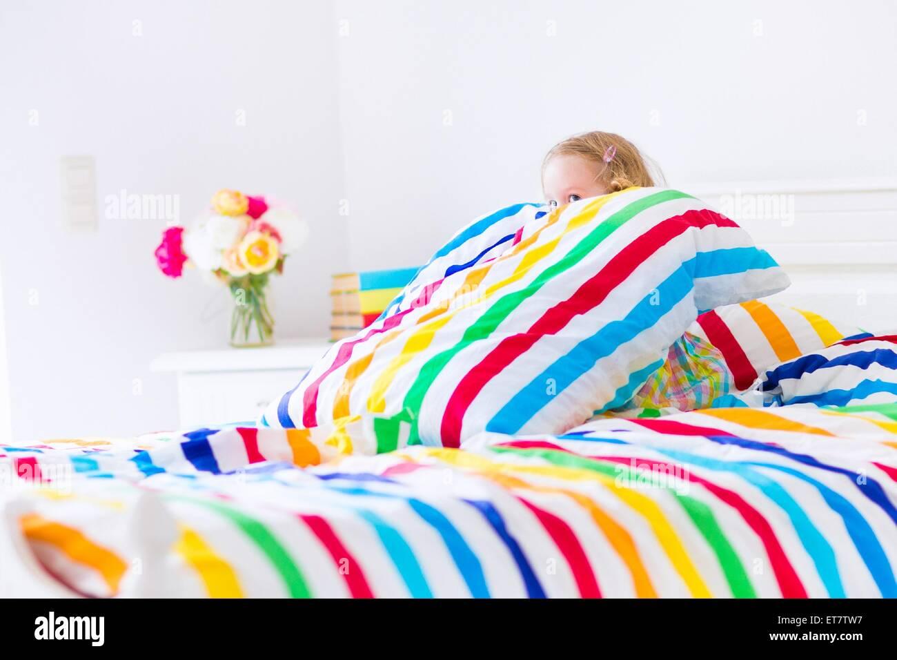 Lustiges kleines Kleinkind Mädchen sitzt in einem weißen Bett mit regenbogenfarbenen Streifen Kissen und Stockbild