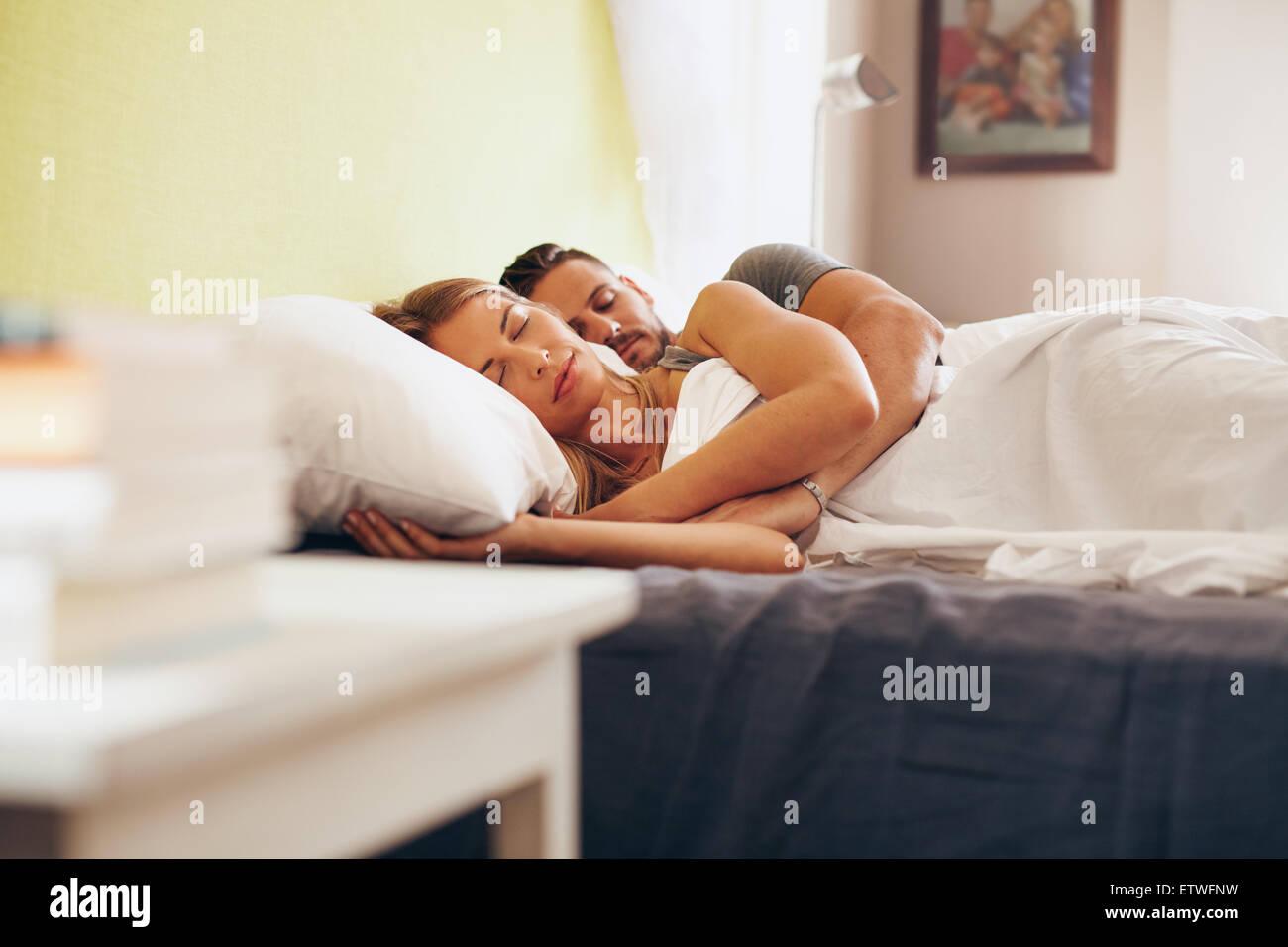 Junge Erwachsene paar friedlich schlafend auf dem Bett im Schlafzimmer. Junger Mann umfassenden Frau liegend schlafend Stockbild