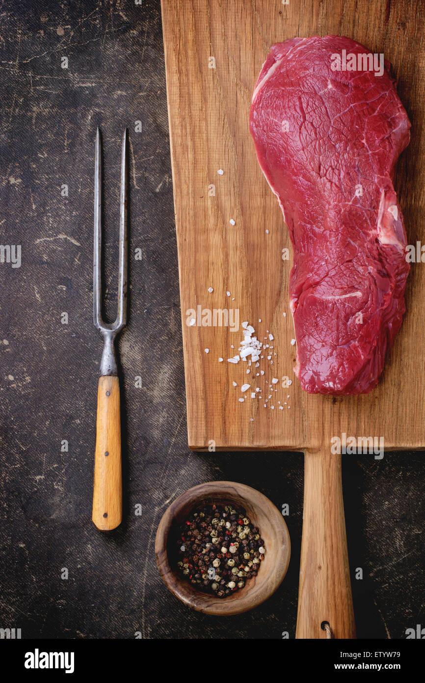 Rohes Steak mit Salz und Pfeffer, serviert auf Holzbrett mit Fleischgabel auf dunklem Hintergrund. Draufsicht Stockbild