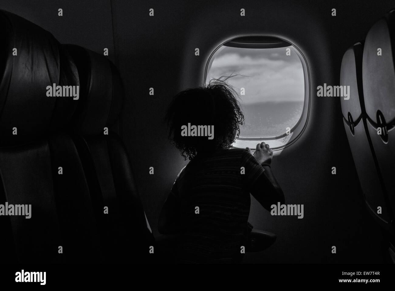 Rückansicht eines Mädchens Blick aus dem Fenster auf einer Ebene Stockbild