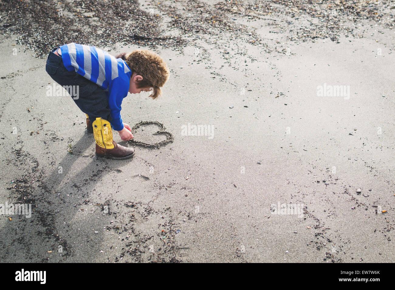 Junge in Cowboystiefeln und Waschbär Hut zeichnen ein Herz in den sand Stockbild
