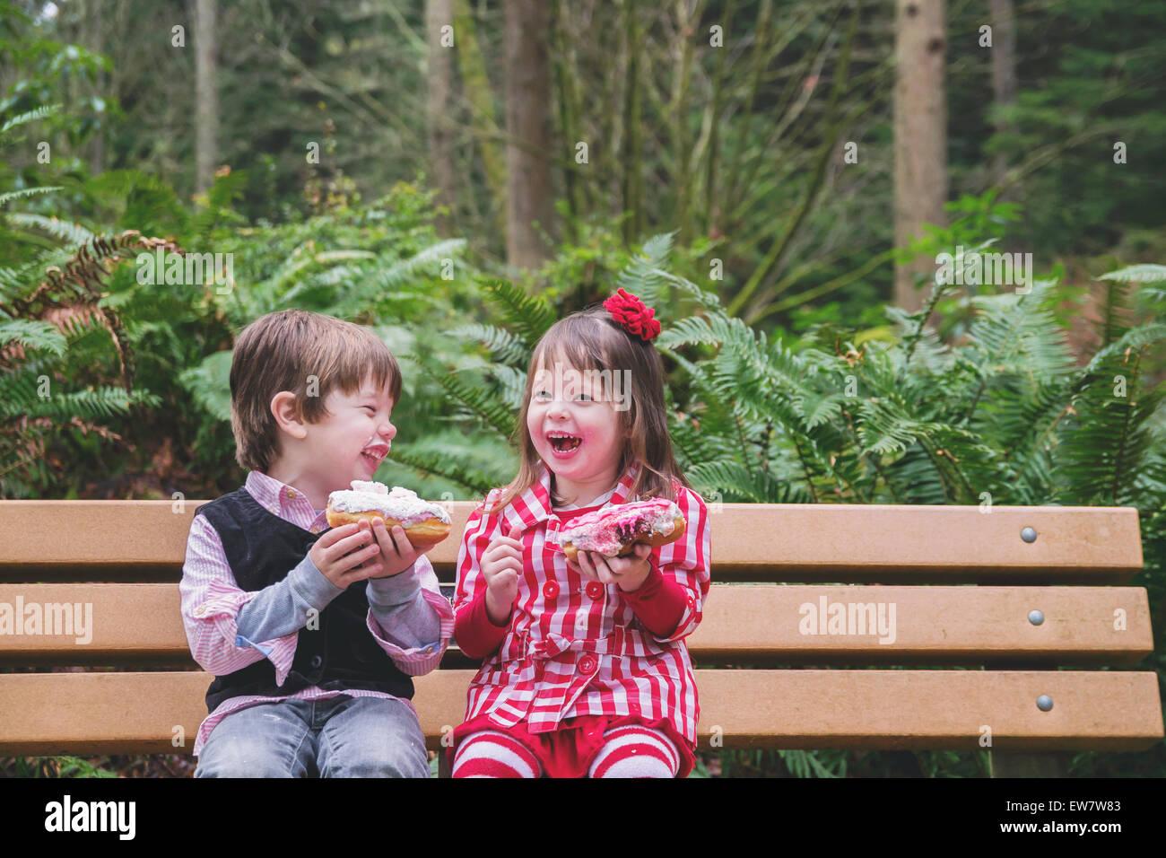 Zwei Kinder sitzen auf einer Bank Lachen und Essen donuts Stockbild