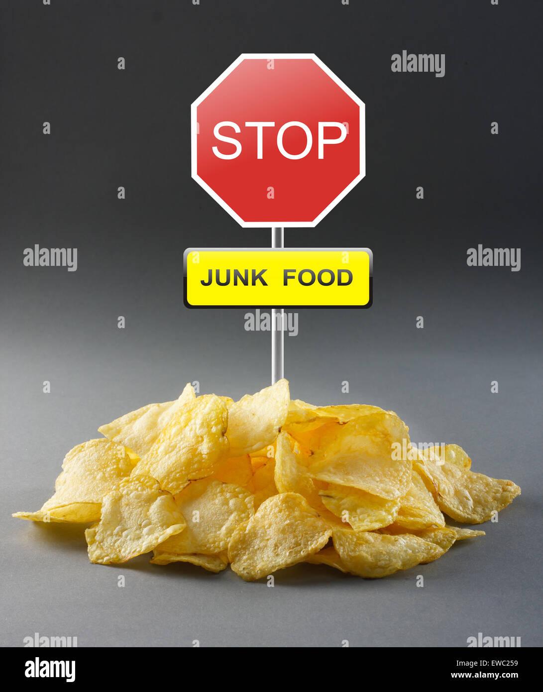 Junk-Food Konzept - Kartoffelchips und Road Stop-Schild Stockbild