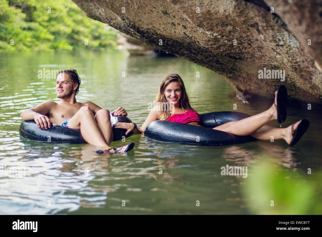 Ein junges Paar Röhren einen Fluss hinunter. Stockbild