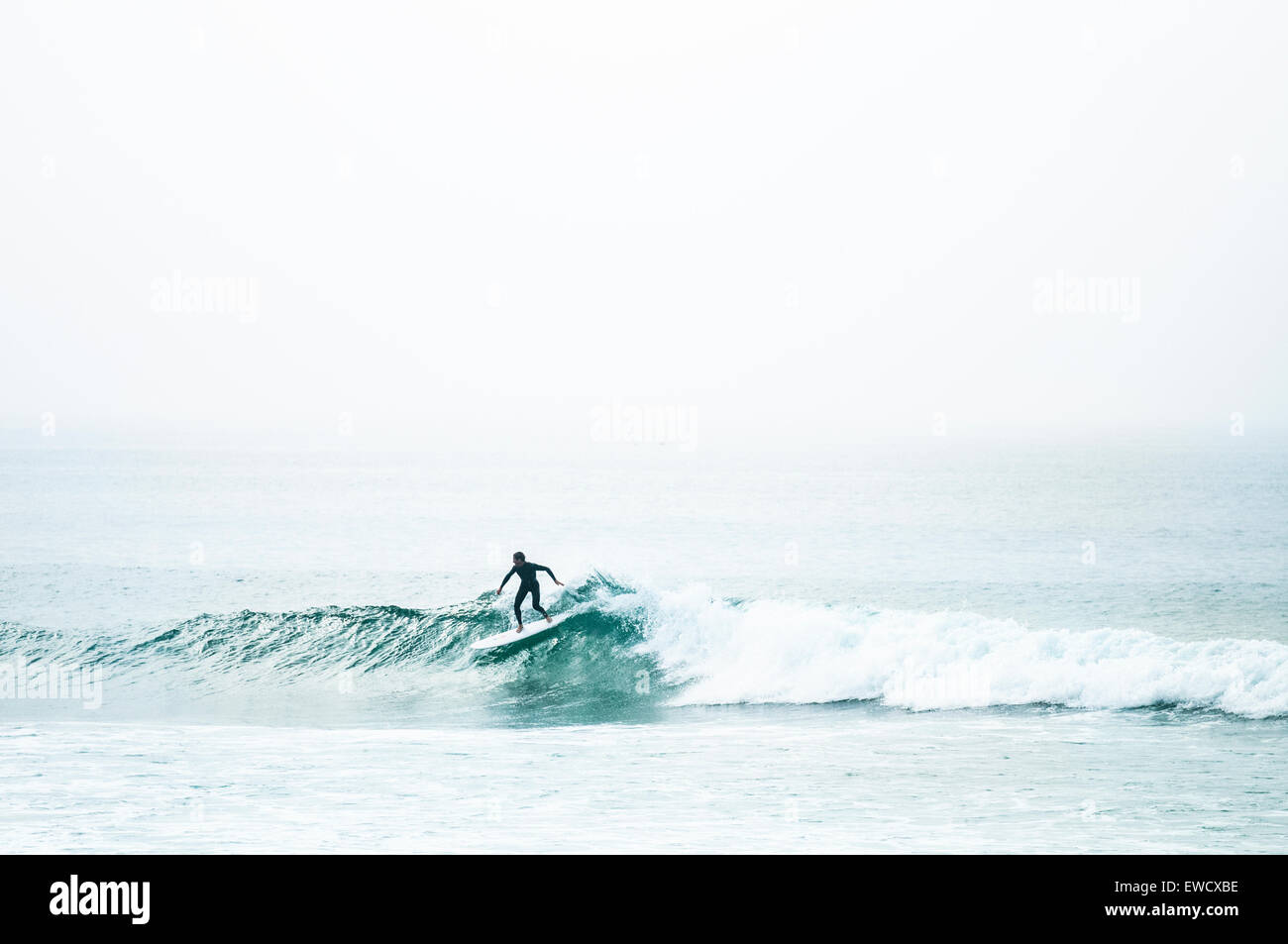Surfer nach unten schieben einer Glasigen grüne Welle in Cornwall. Stockbild