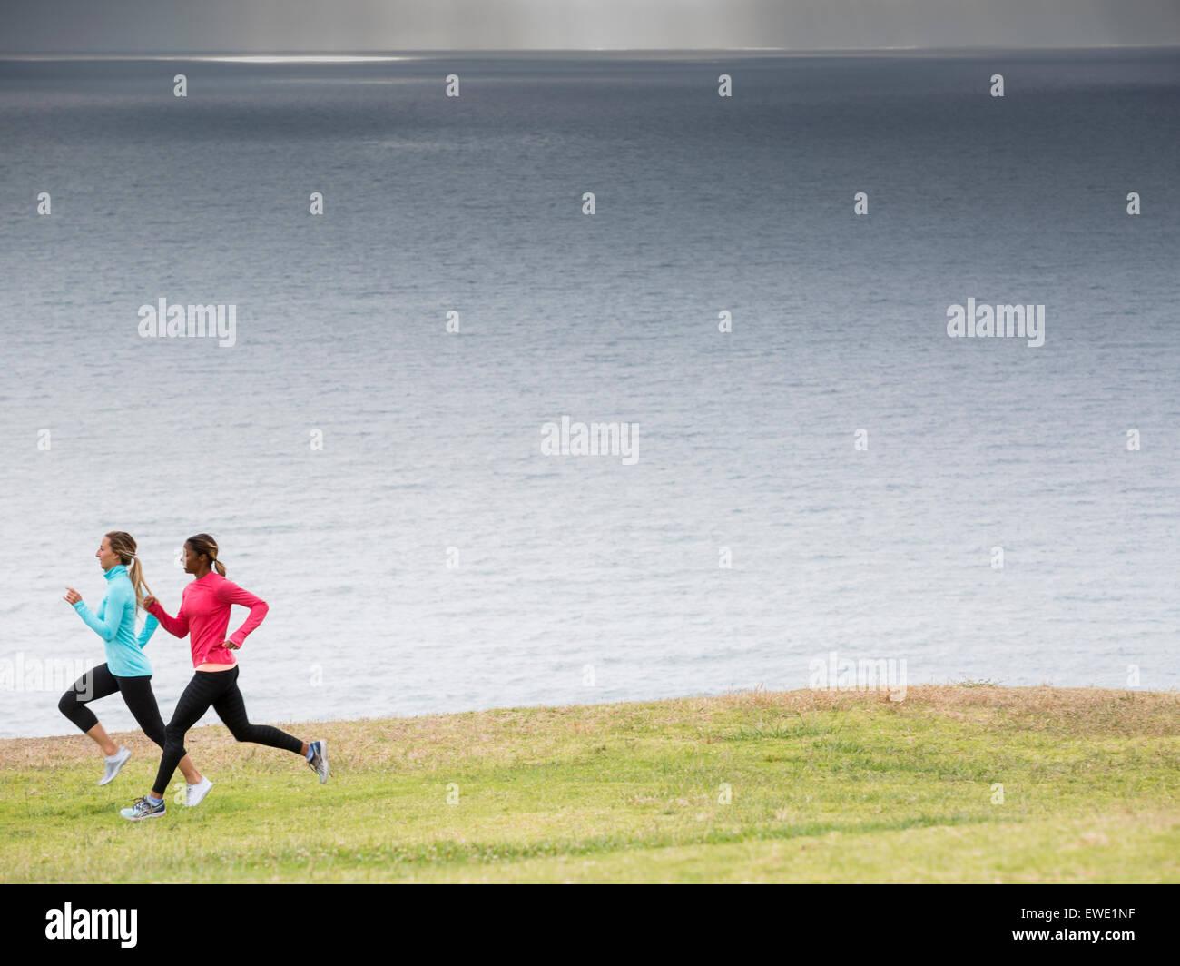 Zwei Frauen Joggen entlang der Küste Stockbild