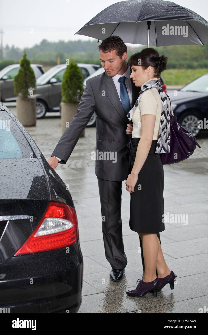 Junger Mann Türöffnung des Autos für die Frau Stockbild