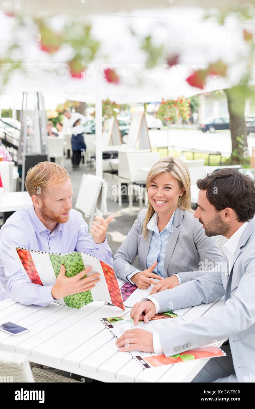 Porträt von glücklich Geschäftsfrau mit männlichen Kollegen Menü im Straßencafé Stockbild