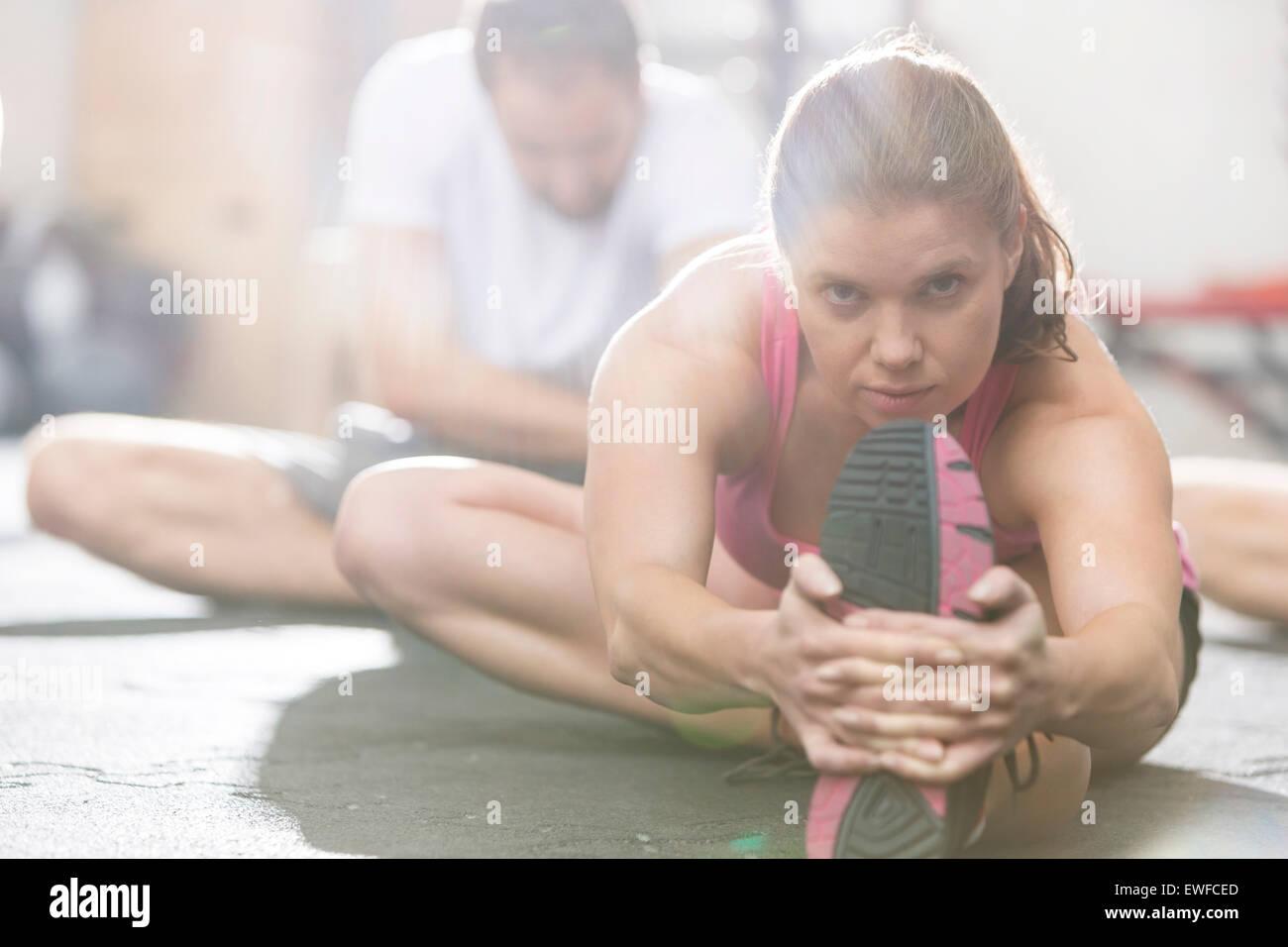 Porträt der selbstbewusste Frau tun stretching-Übung im Crossfit gym Stockbild