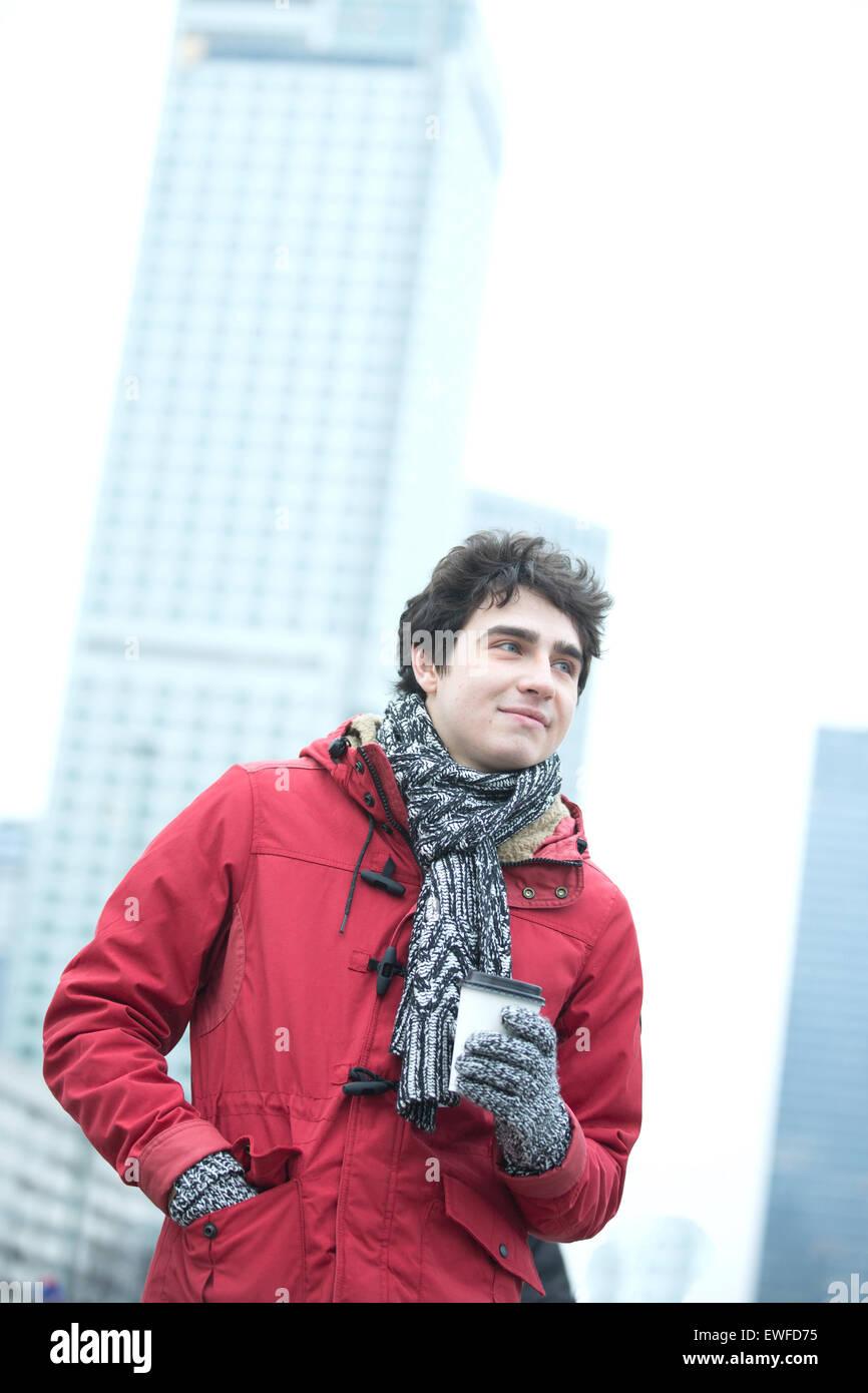 Nachdenklicher Mann in warme Kleidung Einweg-Cup im Freien halten Stockbild