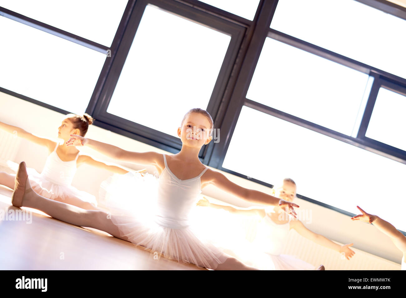 Hübsche kleine Ballerina in Ballett Klasse sitzen auf dem Holzboden in einem hellen, sonnendurchfluteten Dance Stockbild