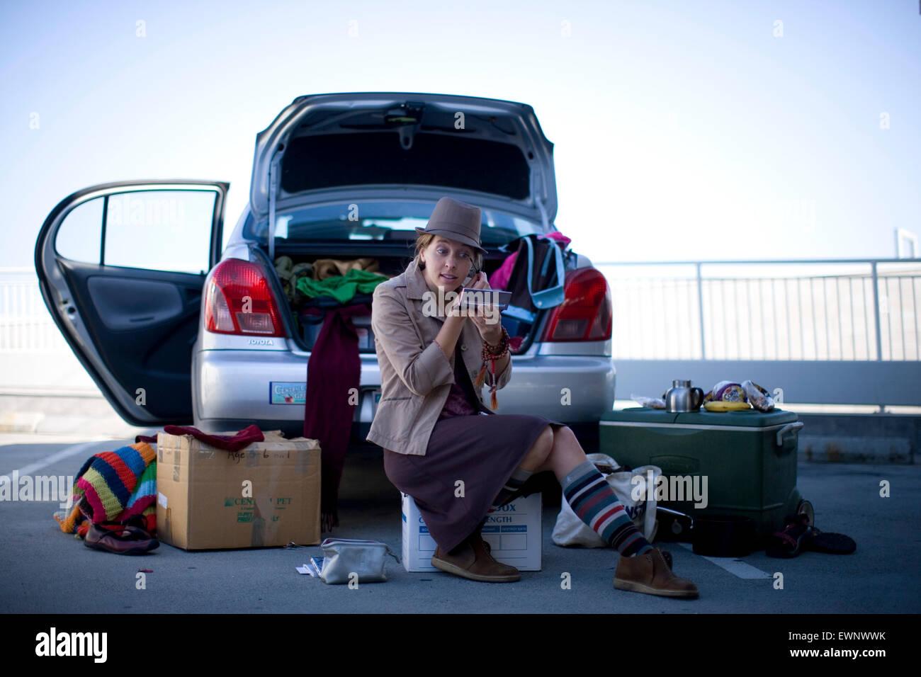Eine angehende Schauspielerin gilt Make-up vor einem Vorsprechen, sitzend unter ihr Hab und gut in den Kofferraum Stockbild