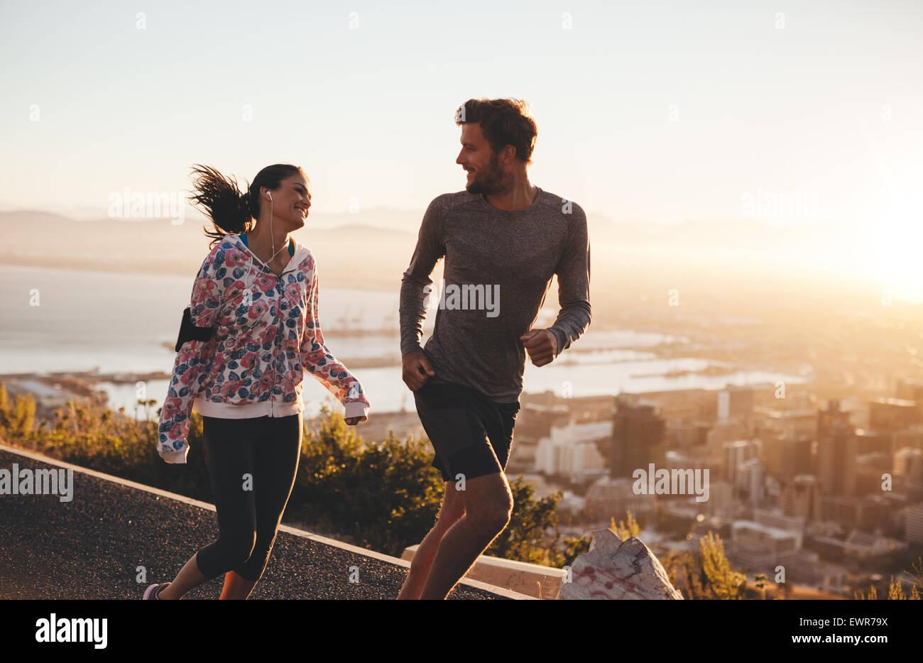 Junges Paar laufen zusammen im Freien. Glücklicher junger Mann und Frau, Joggen auf Landstraße bei Sonnenaufgang. Stockbild