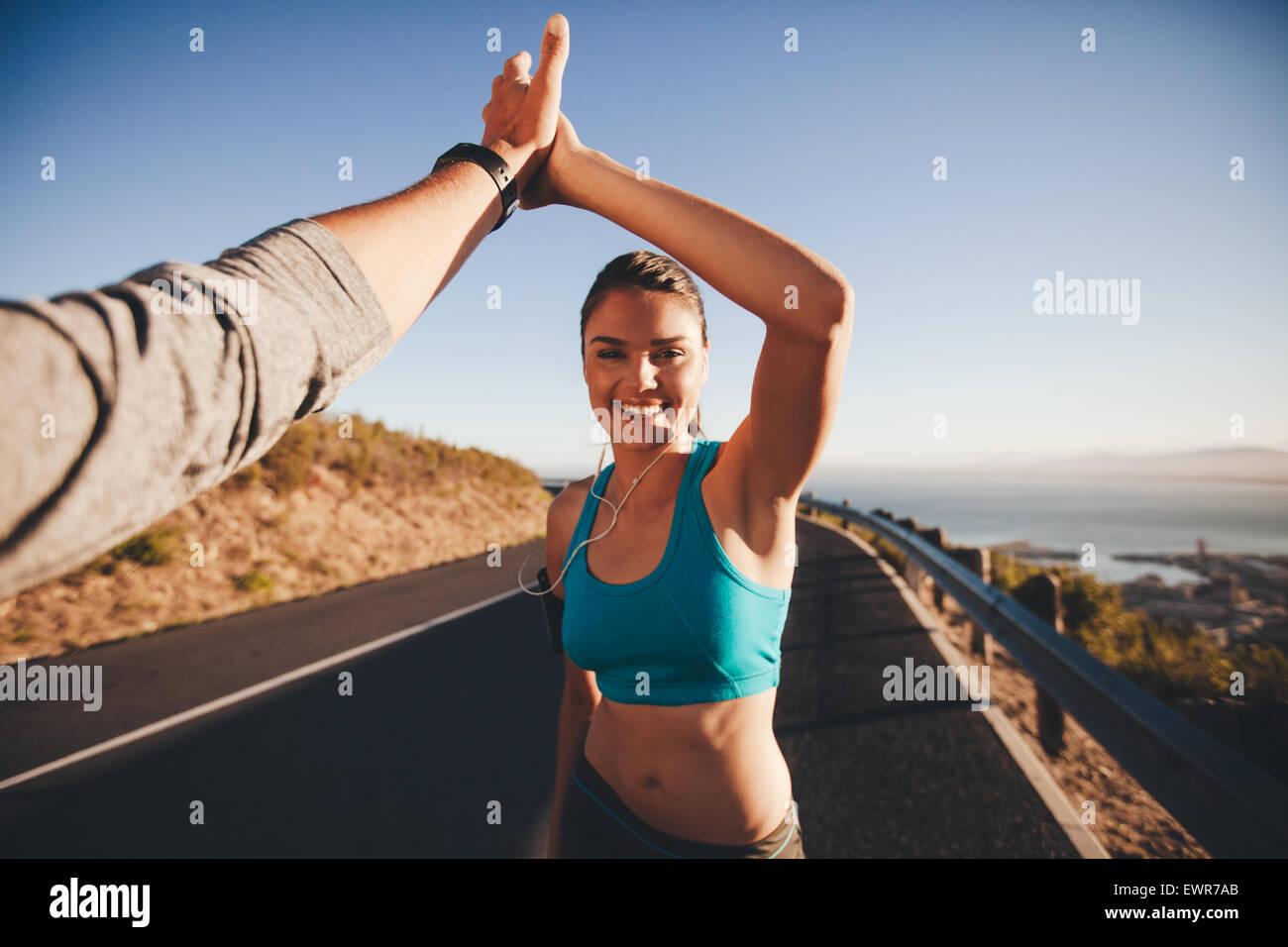 First-Person-Ansicht von Mann und Frau ein high Five zu tun. Glückliche junge Frau geben hohe fünf man Stockbild