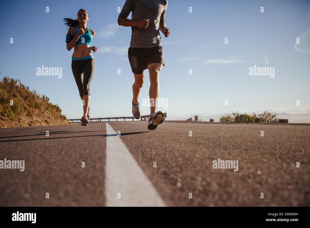 Niedrigen Winkel Schuss der jungen Frau rennt unterwegs mit Mann vorne an einem Sommermorgen. Läufer, die Ausbildung Stockbild