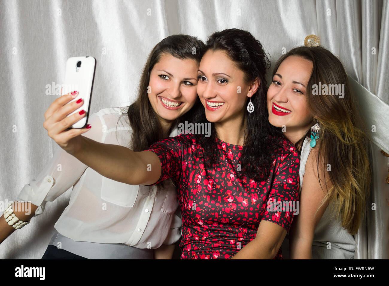 Gruppe junger fröhlich lächelnde Frauen machen Selfie. Drei Schönheit Mädchen haben Spaß Stockbild