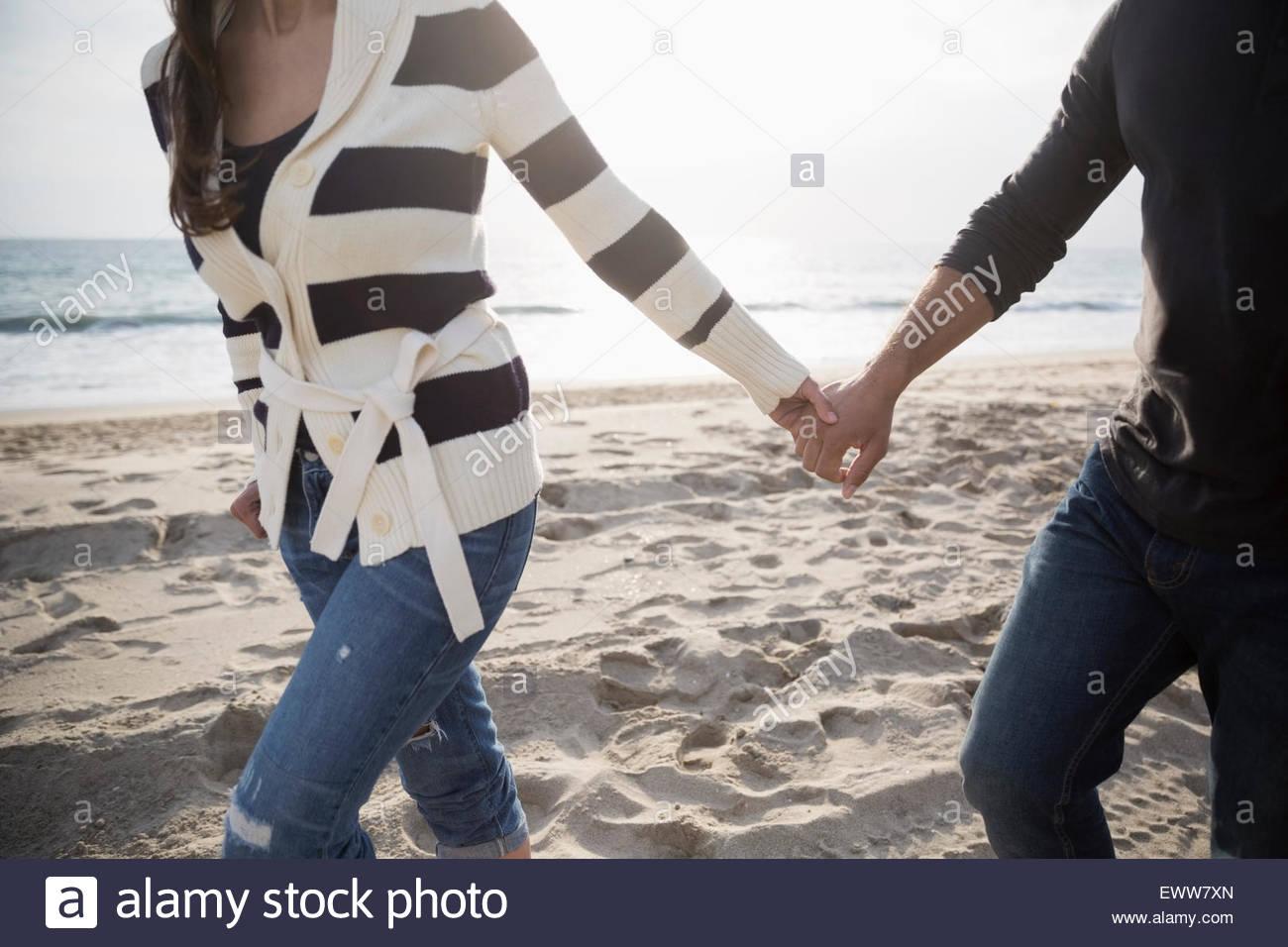 Paar Hände halten und zu Fuß am Strand. Stockbild
