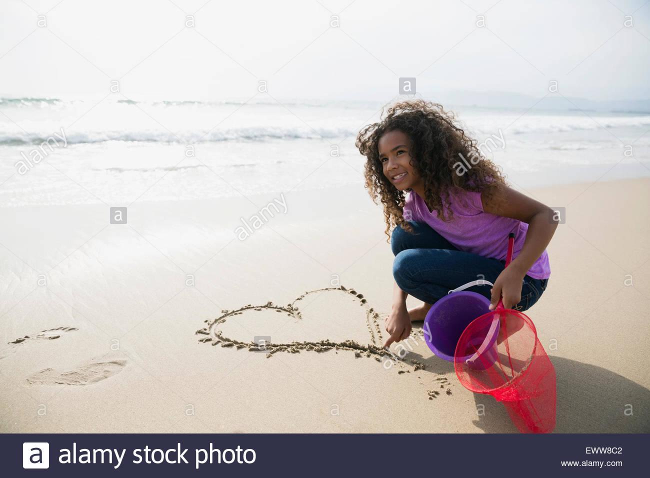 Mädchen zeichnen Herzform in Sand am Strand Stockbild