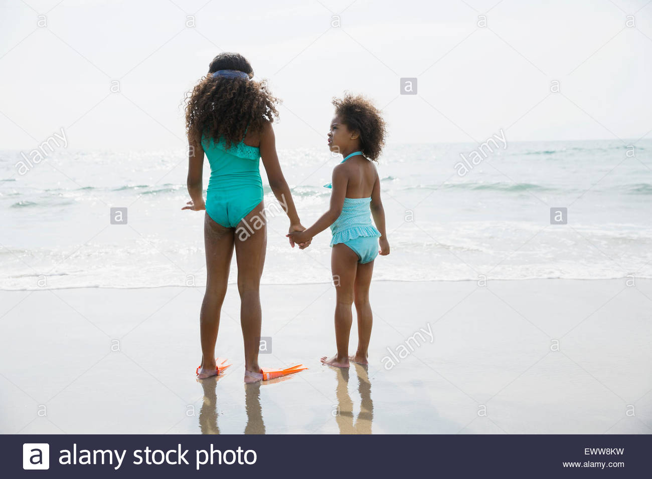 Schwestern in Badeanzügen, die Hand in Hand am Strand Stockbild
