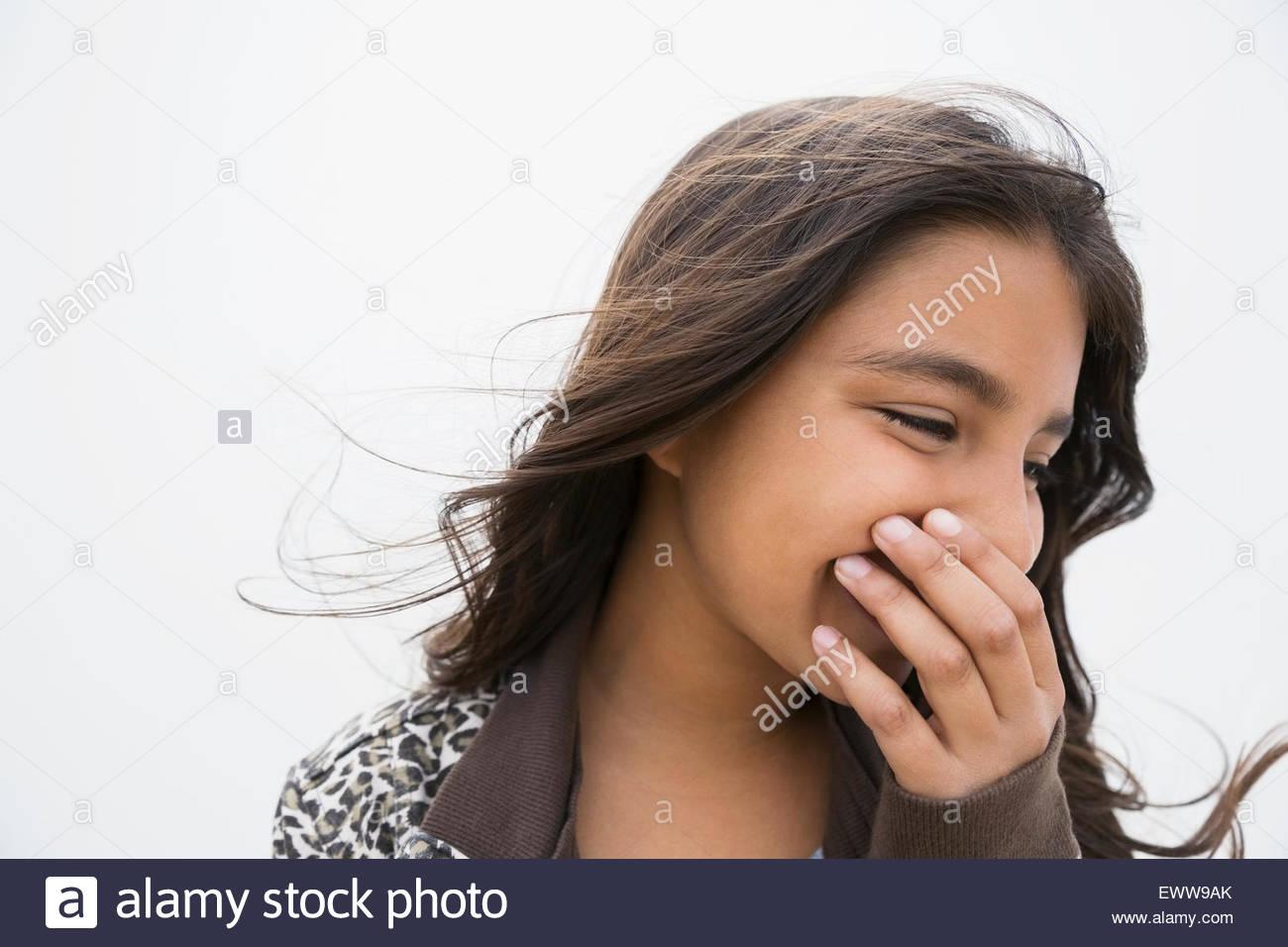 Brünette Mädchen Lachen Verkleidung Mund mit der hand Stockbild