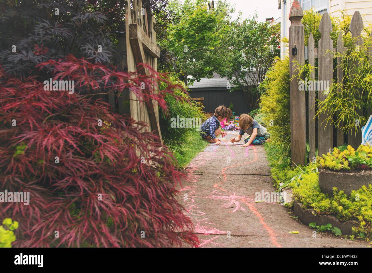 Drei kleine Kinder, die Zeichnung mit Kreide auf einem Pfad in einem Garten Stockbild