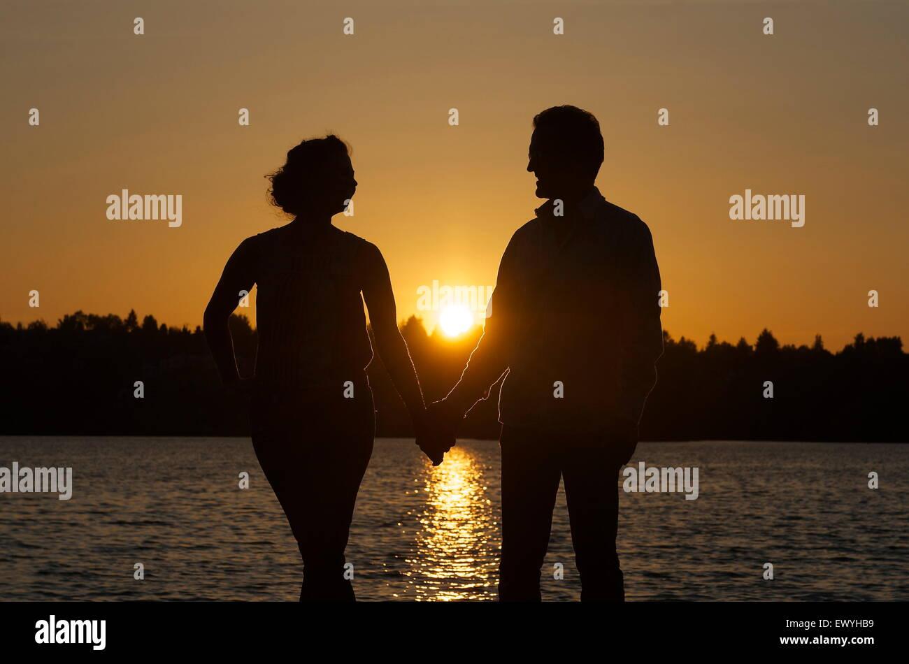 Silhouette von ein paar Hand in Hand Stockbild