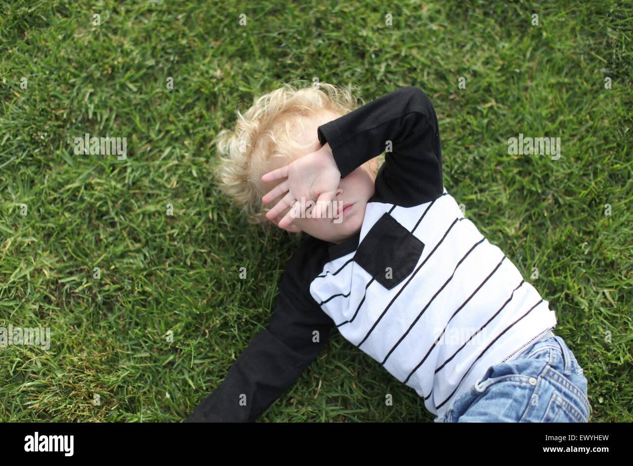 Junge mit Hand bedeckte Gesicht auf dem Boden liegend Stockbild