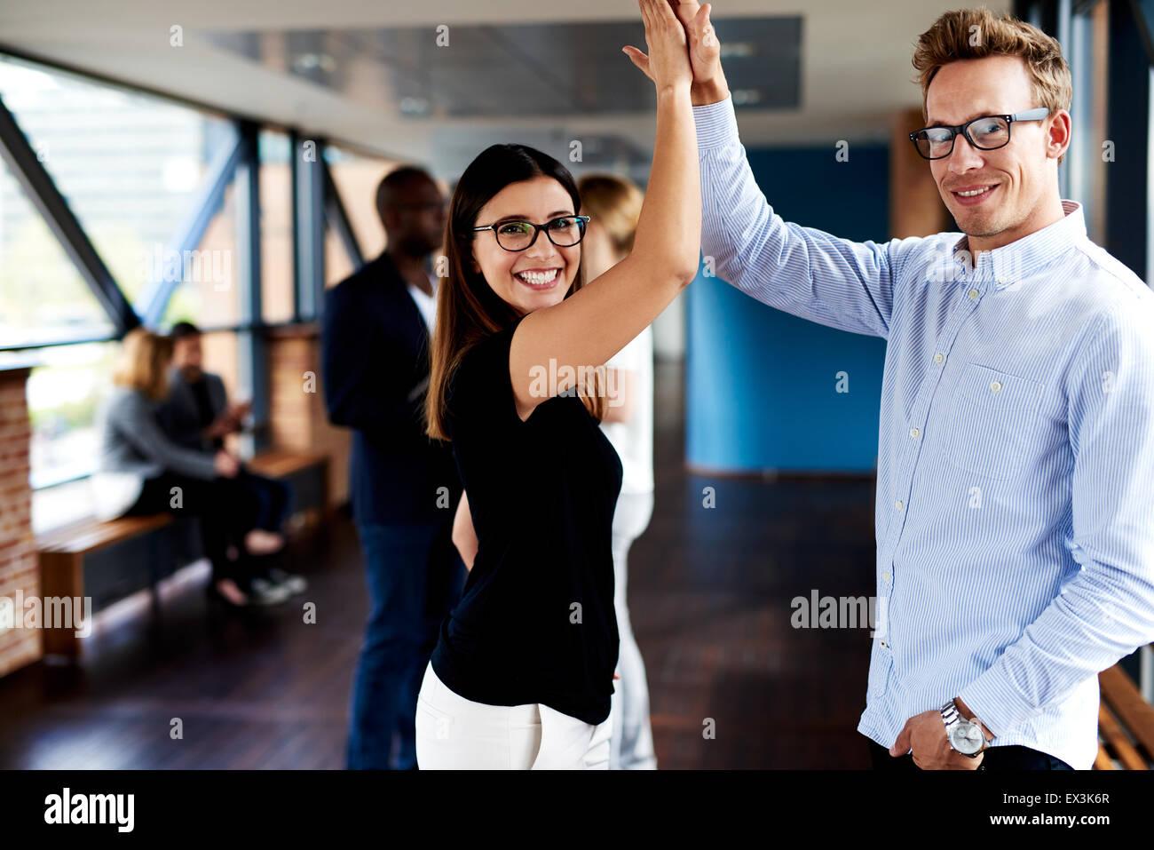 Weibliche und männliche Kollegen hohe FIVING und lächelnd an Kamera Stockbild