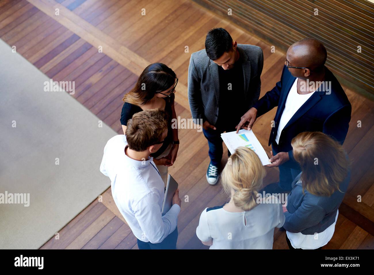 Blick hinunter auf der Suche nach Kollegen in einem Kreis stehen mit Blick auf die Charts auf den Unterlagen Stockbild