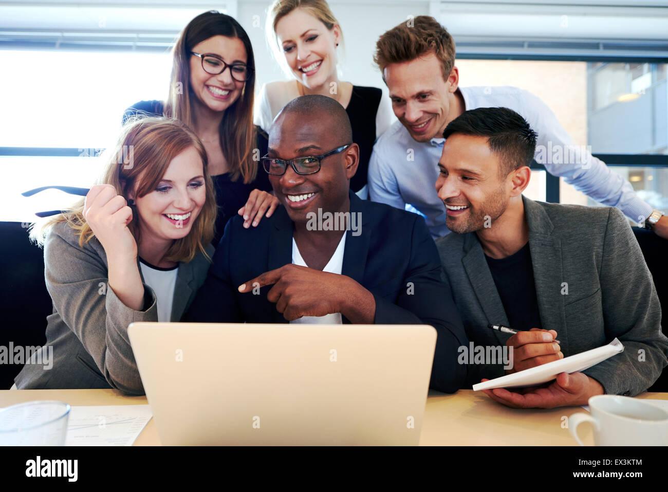 Schwarze männliche Executive lächelnd an Kamera mit Kollegen versammelte sich um ihn und Laptop Stockbild