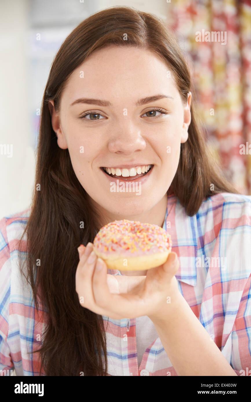 Portrait Of Smiling Teenager-Mädchen auf den Verzehr von Donut Stockbild