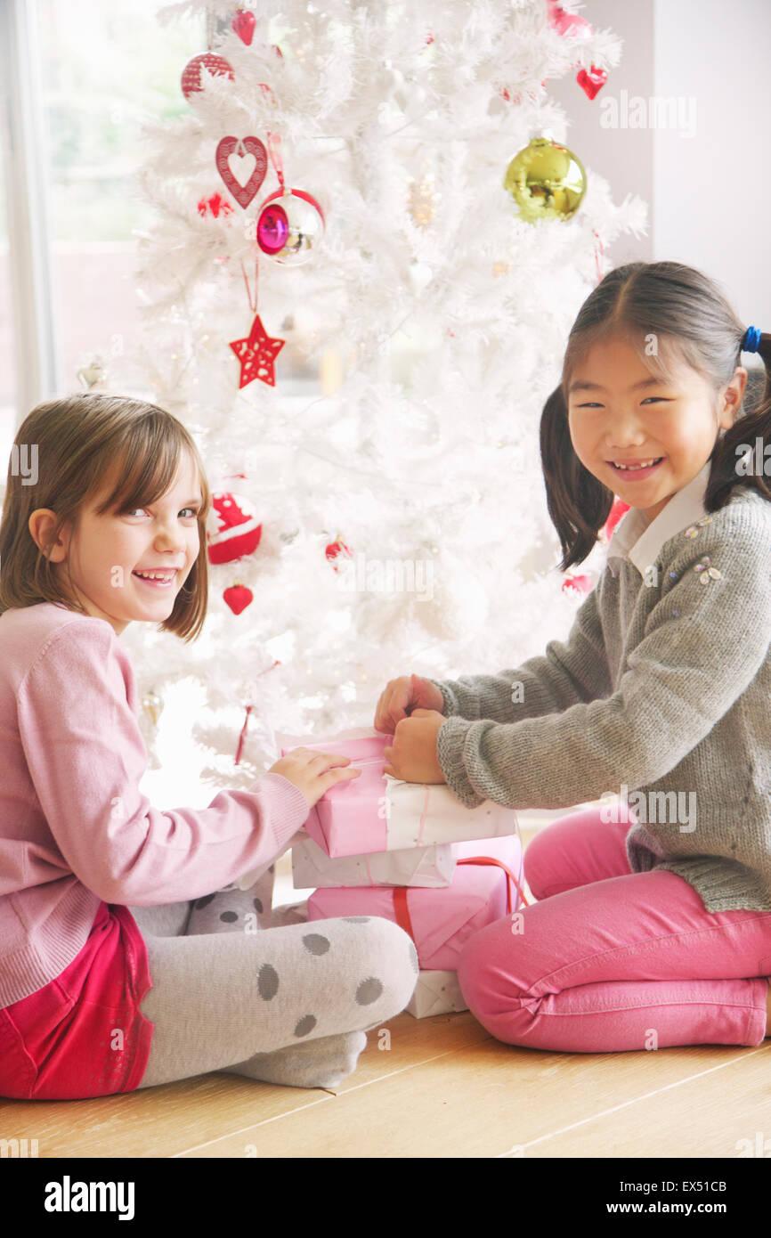 Zwei junge Mädchen Eröffnung präsentiert unter Weihnachtsbaum, Lächeln Stockbild