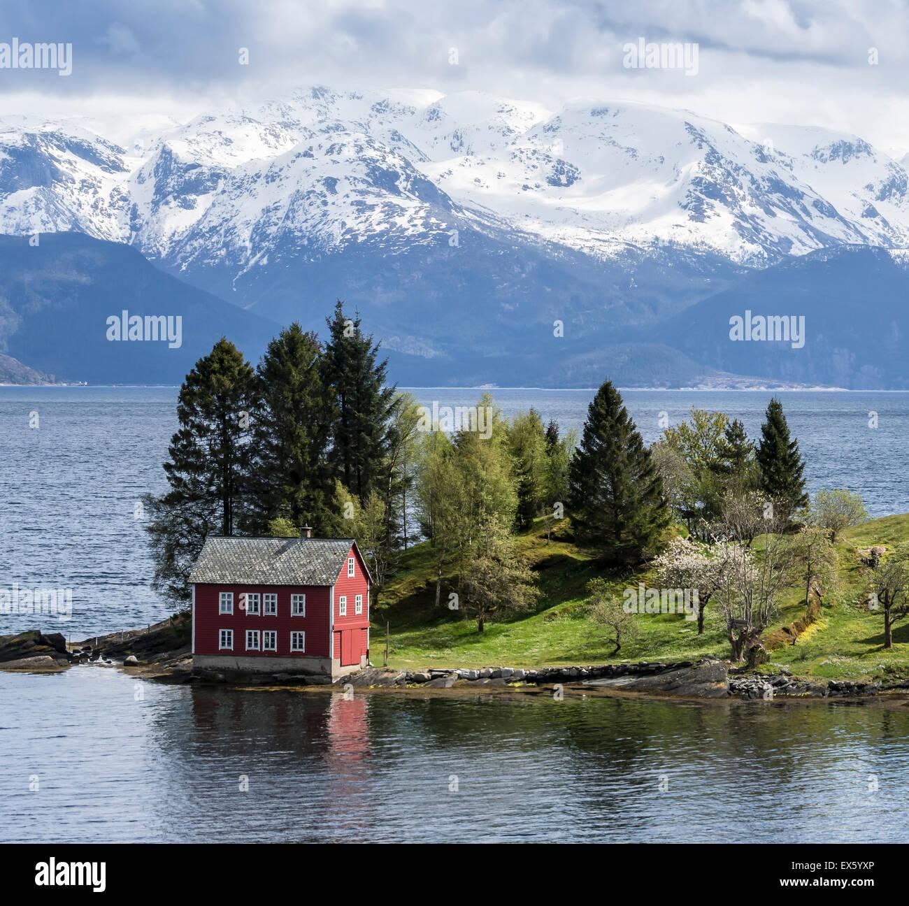 Typischen roten Haus auf einer Insel in den Hardangerfjord, in der Nähe von Strandebarm, Hordaland, Norwegen Stockbild