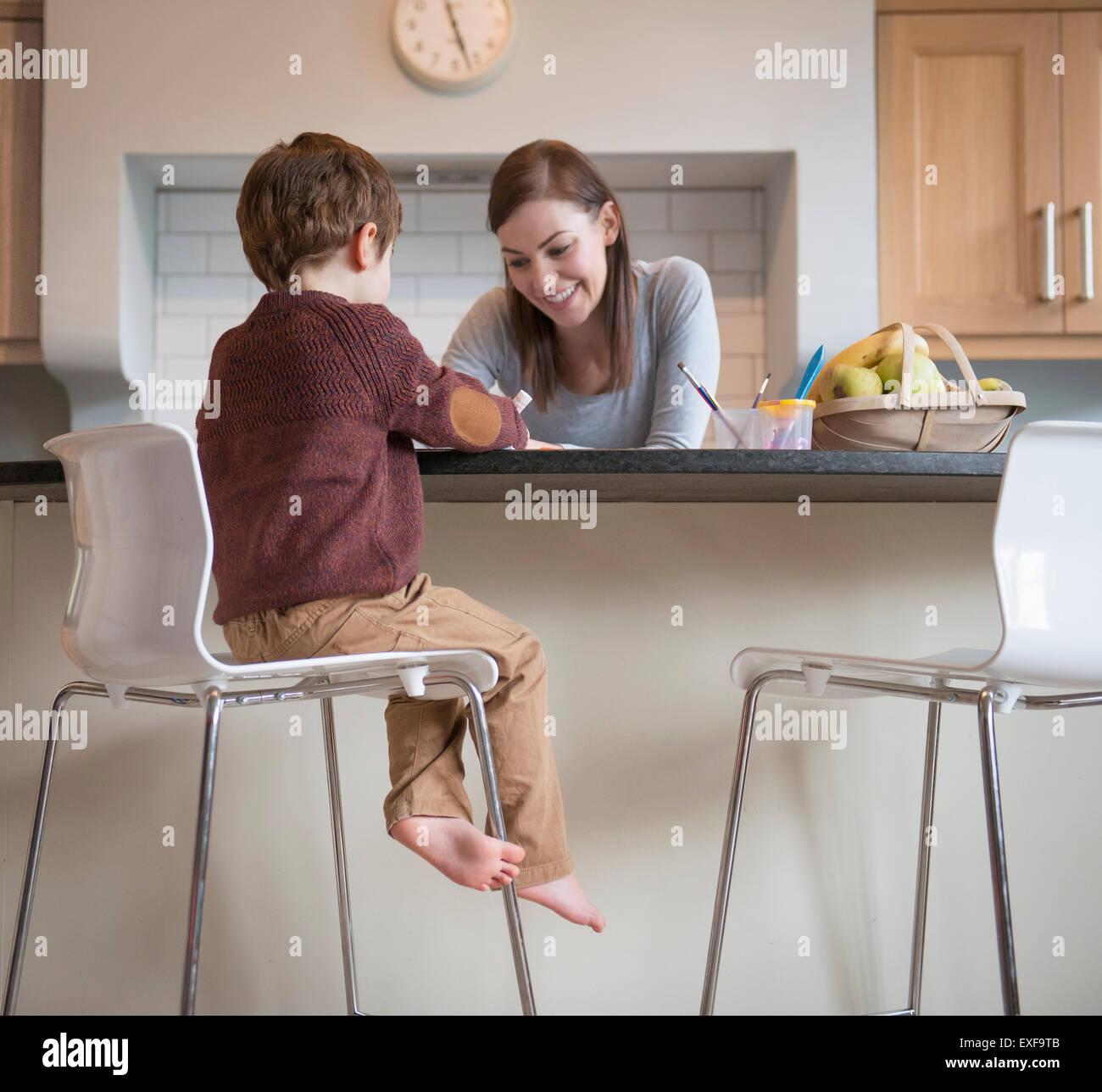 Junge mit Mutter in der Küche und Zeichnung auf Hocker sitzend Stockbild
