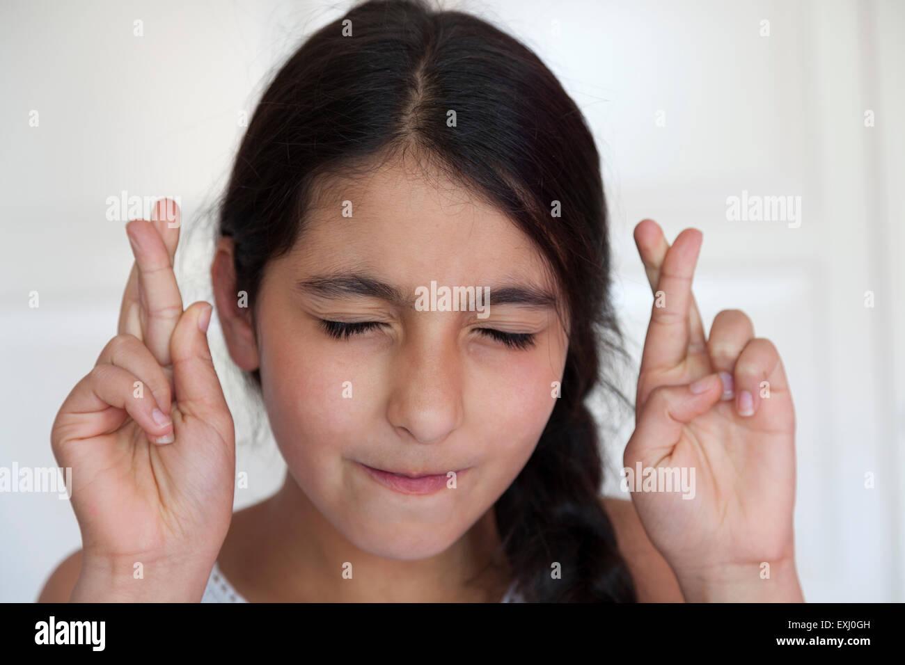 Teenager-Mädchen ihre Daumen mit geschlossenen Augen Stockbild